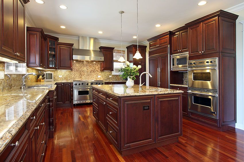 Wood kitchen kitchen in luxury home with dark cherry wood cabinetry, wood flooring, and PMJOSMJ
