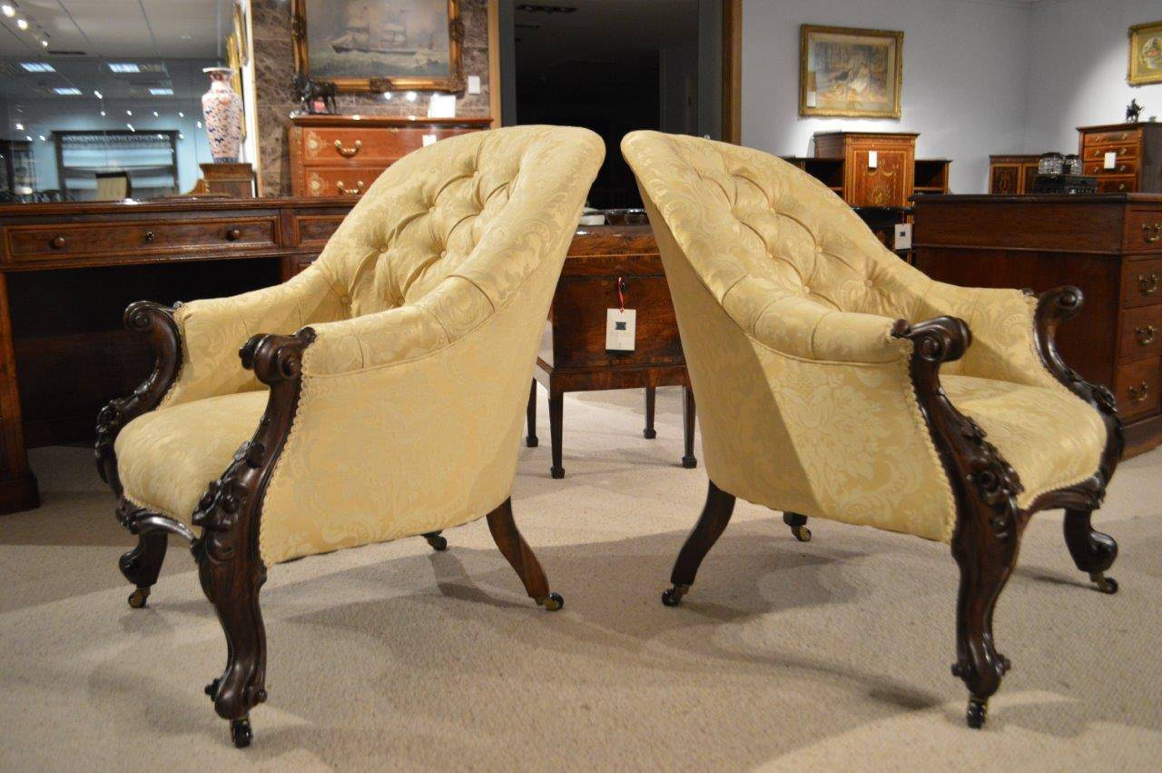 Pair of carved solid rosewood Victorian Period deep buttoned antique  armchairs. Each with a beautiful