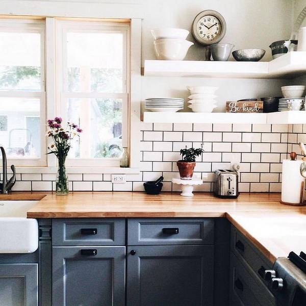White-tiled walls and backsplash with gray grout give more warmth to this  farmhouse kitchen