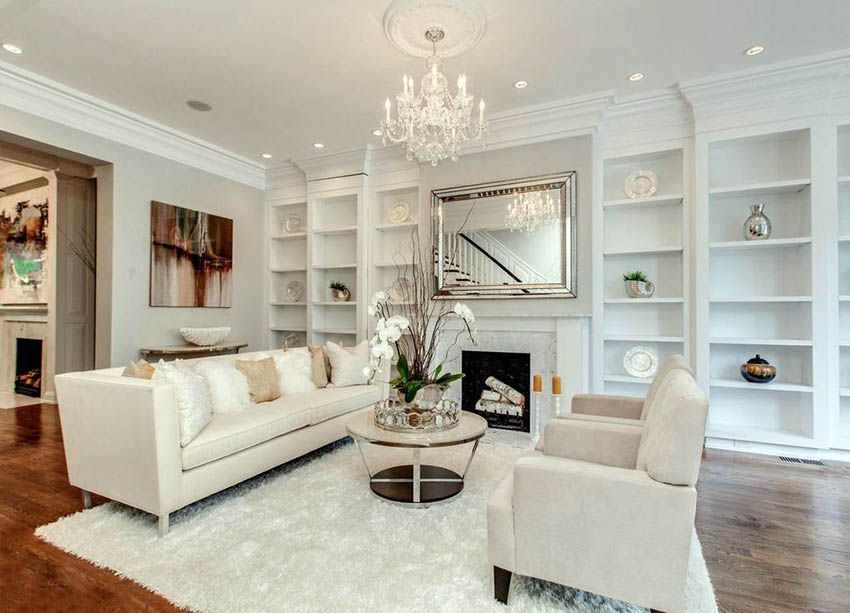 Beautiful white living room with built in bookshelves, shag carpet, wood  floors and chandelier