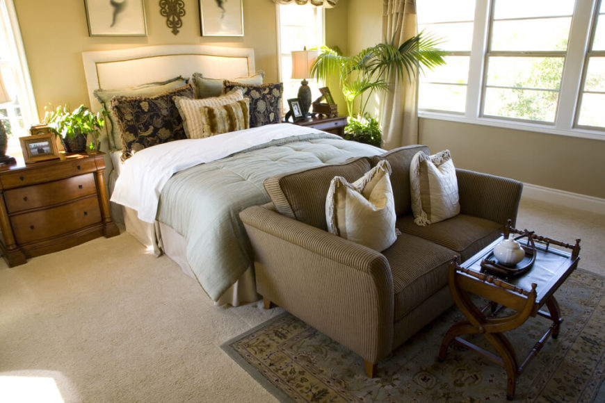 At the foot of the bed is a low-profile corduroy loveseat with a small