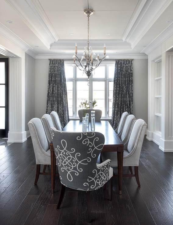 Gray dining room features a tray ceiling accented with a satin nickel and  glass chandelier illuminating a dark stained curved dining tab…