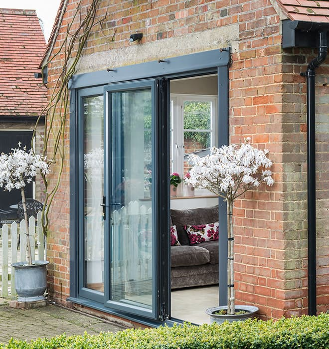 A beautiful set of black aluminium bi-folding doors slightly open