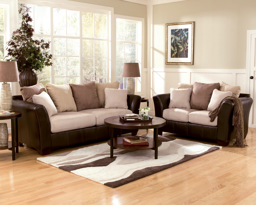 simple living room design on hardwood floor with patterned area rug and  round coffee table with