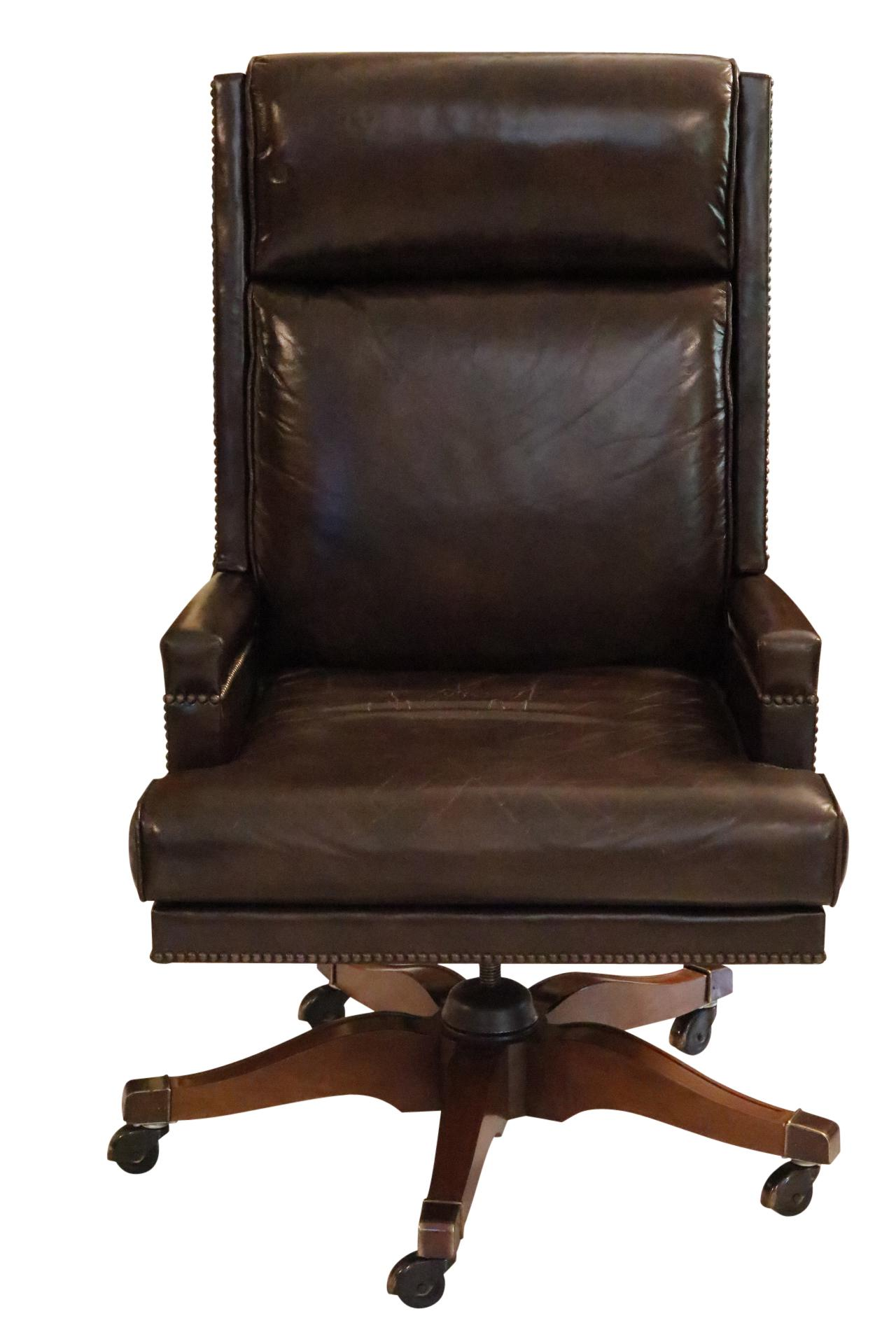 An executive leather desk chair made by Baker Furniture. Brown leather is  secured with brass