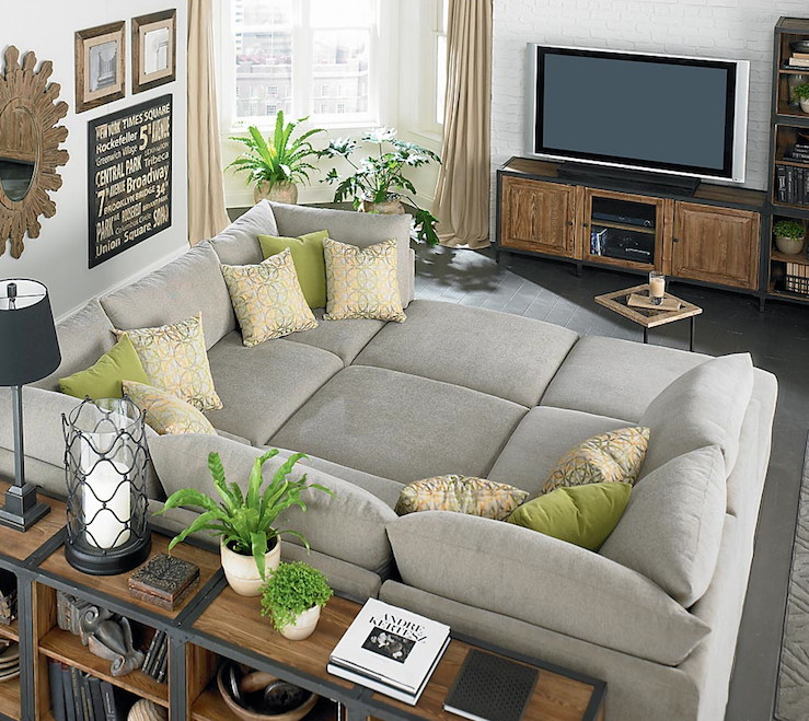 Huge gray Bassett Beckham Pit Sectional sofa, green pillows, industrial  bookshelves, subway sign, wood sunburst mirror, exposed brick wall painted  white and
