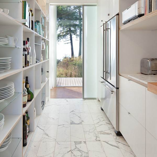 White marble tiles add to the light and airy feel in this compact kitchen.