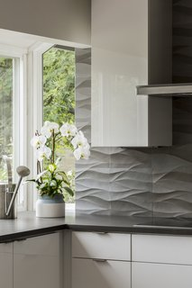 The undulating curves of the natural stone backsplash by Decorative  Materials Inc. work with the