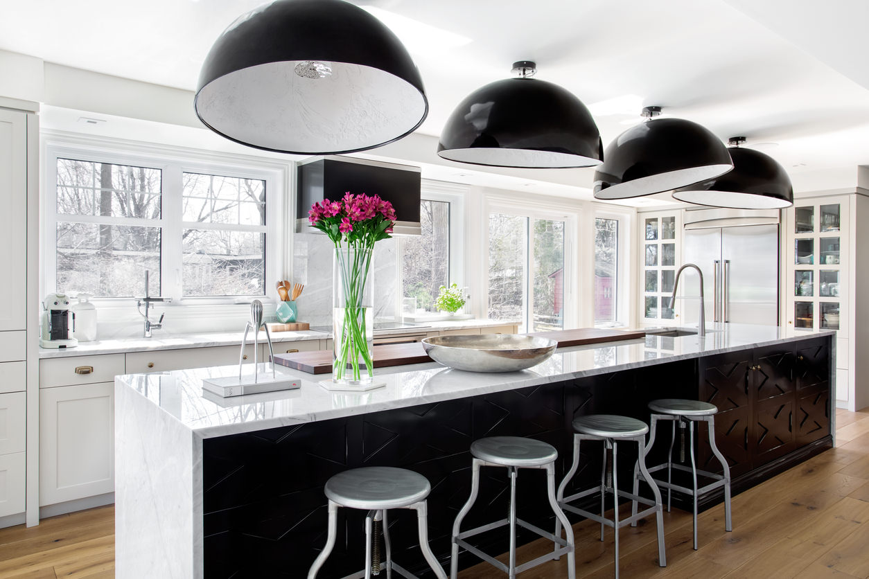 Stunning white and black modern kitchen with medium dark wood flooring.  Actually, this kitchen