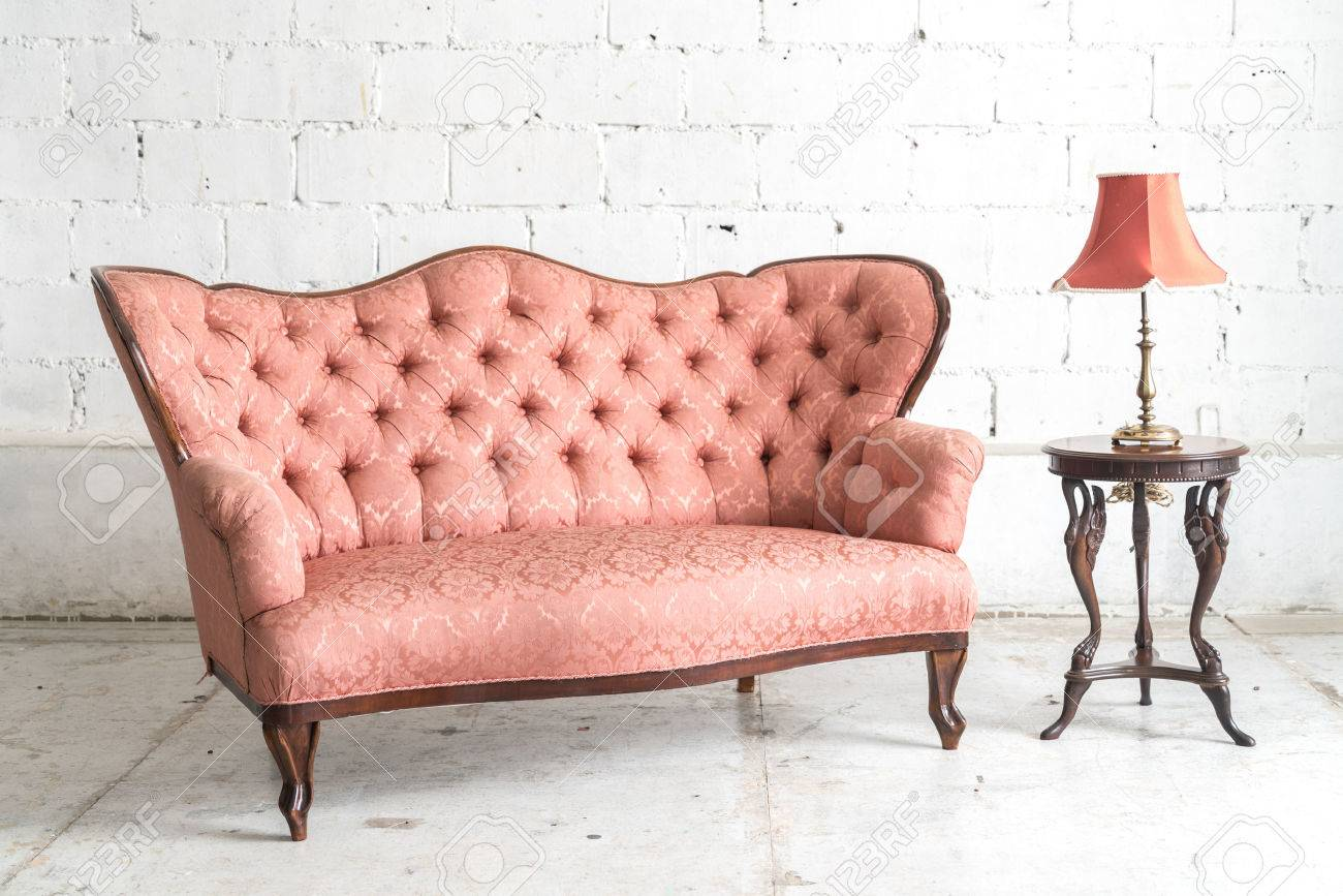 Pink vintage sofa and lamp on white wall. Stock Photo - 60981762