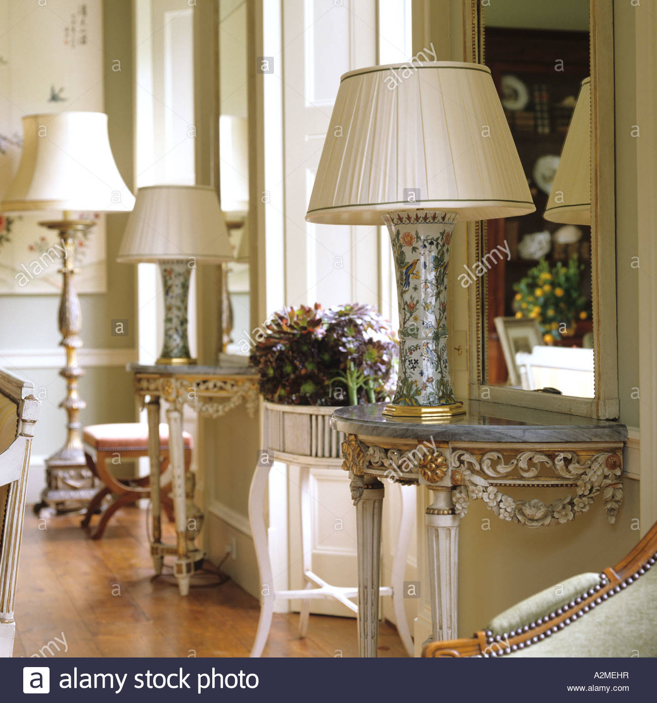 country house lighting marble topped console tables with lamps in drawing room of english country GTKOJTG