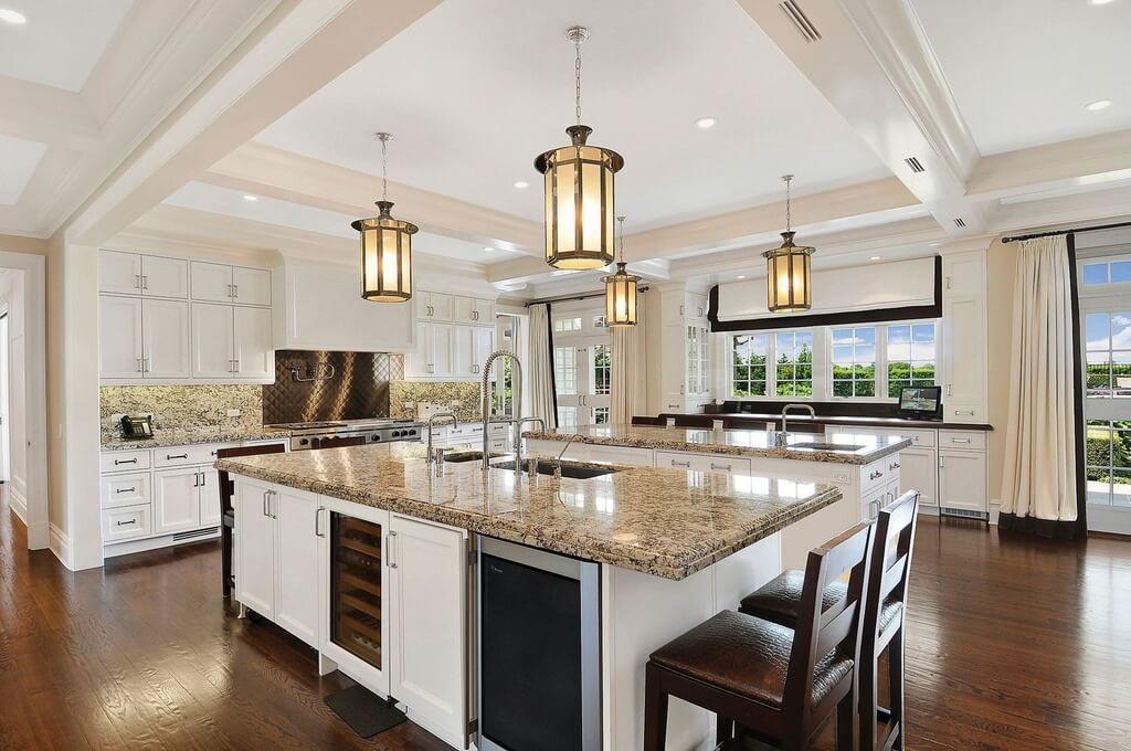 dream kitchens with white kitchen islands huge white kitchen with dark wood flooring. the wall of windows provides KTYBRLW
