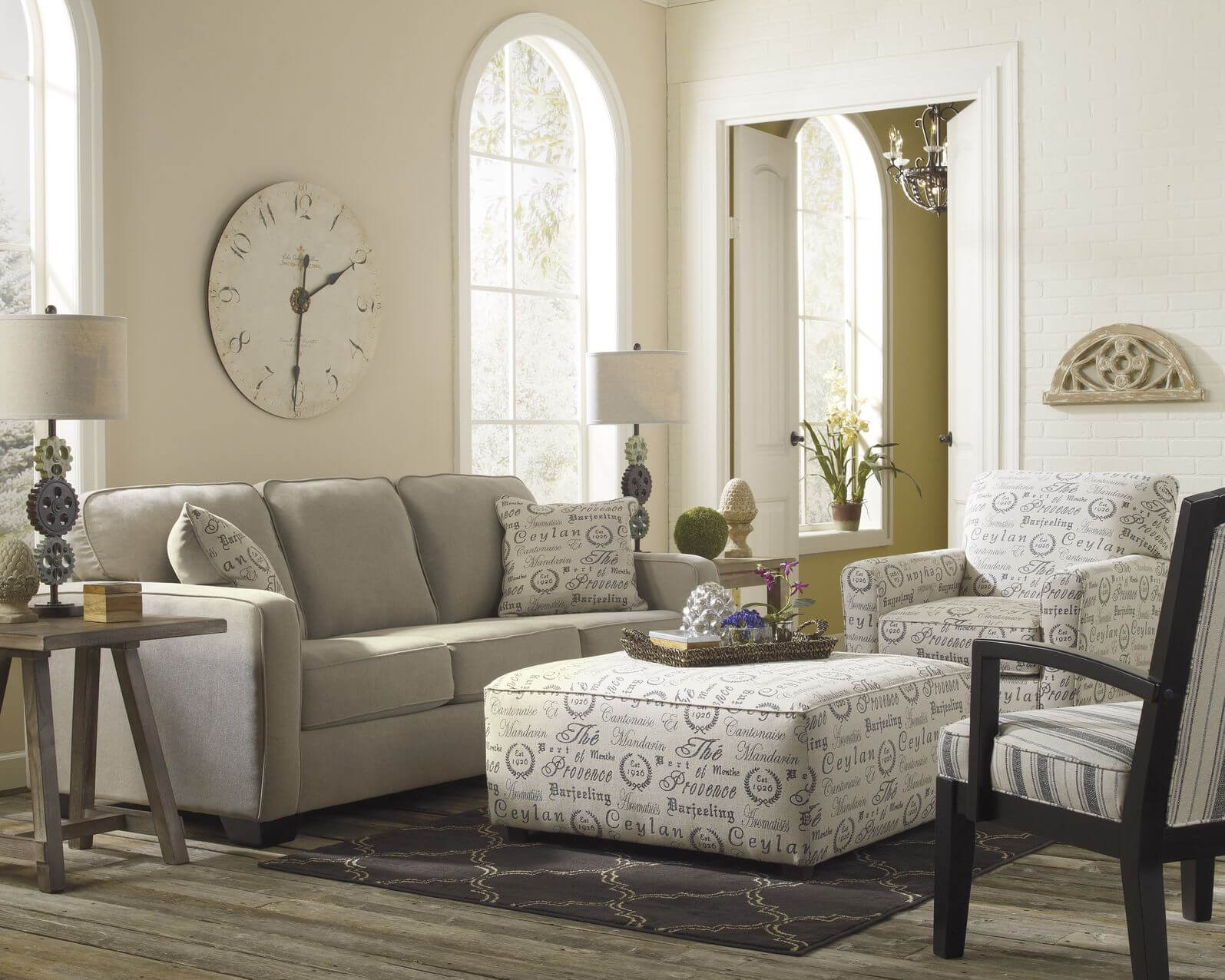Light toned living room stands over grey hardwood flooring, with neutral  grey sofa next to