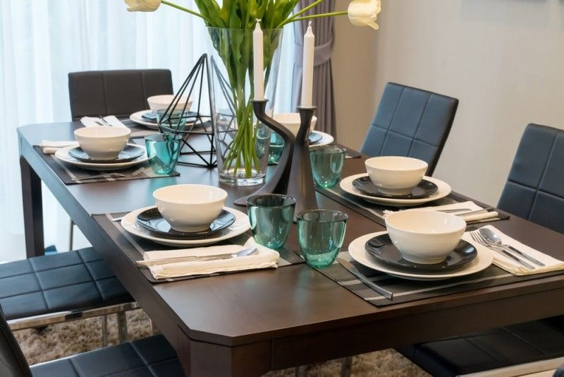 Dark wood dining room table with six place settings, comfortable modern  chairs and large central vase of flowers