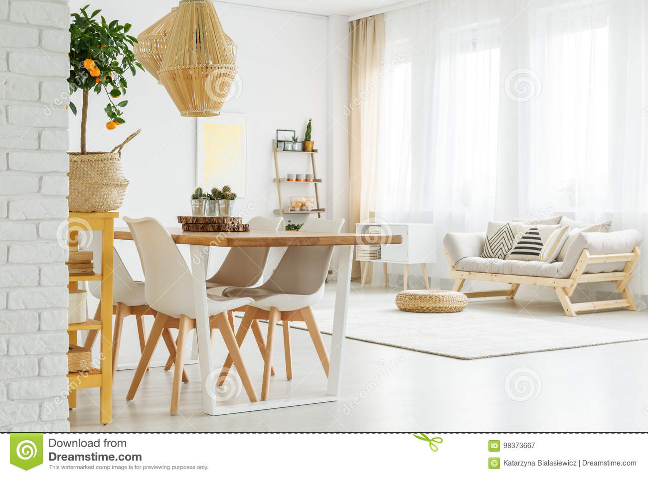 Open space with dinner table, white chairs and comfortable, grey sofa