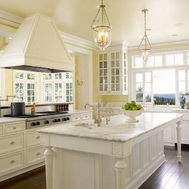Yellow is one of the most popular paint colors for the kitchen, and this  faint hue is as welcoming as a spring garden. Glass-front cabinets and  marble