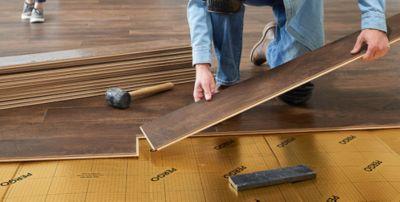 Man installing dark brown laminate flooring over gold underlayment.