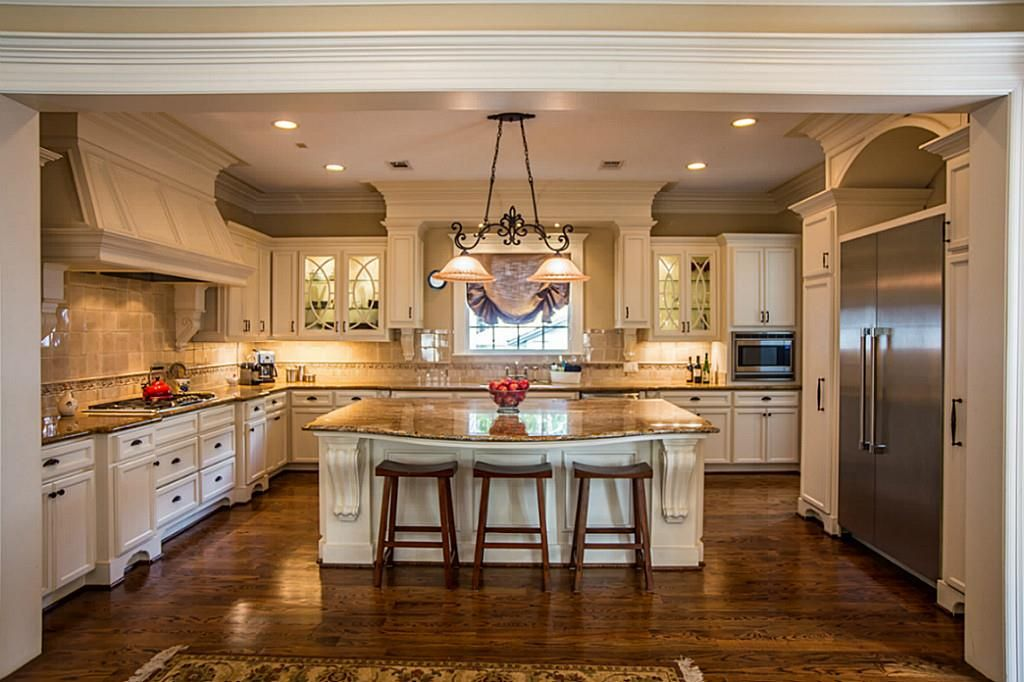 White traditional luxury kitchen with rich wood flooring inu-shape with  center island.